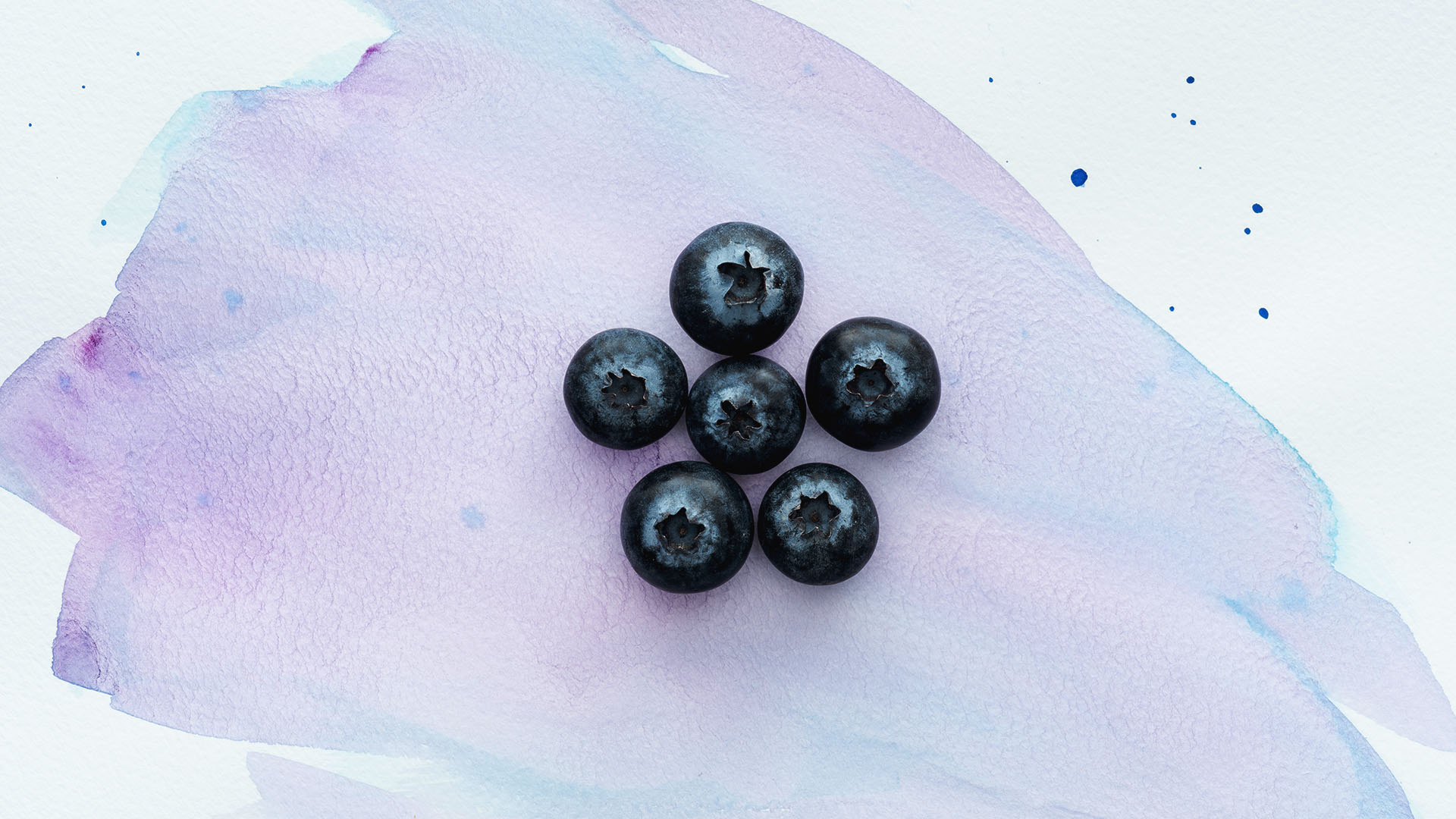 top view of ripe blueberries on white surface with purple waterc